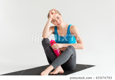 Sporty girl with bottle of water resting on yoga mat after her training, white background 65974793