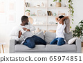 Happy Black Preteen Boy Enjoying Pillow Fight With His Dad At Home 65974851
