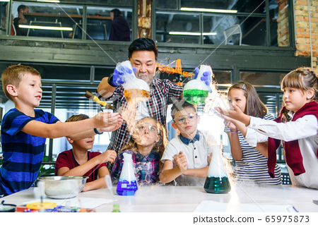 Asian young teacher with group of six cheerful caucasian 8-10 years pupils wearing protective glasses during chemical experiment with colored liquids in modern school. 65975873