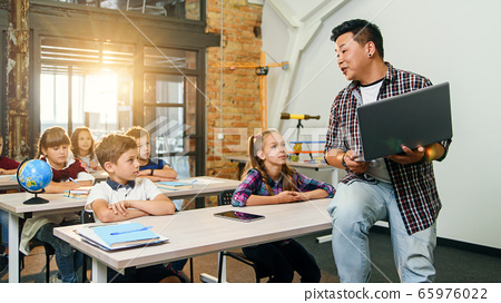 Asian male teacher sits on desk with laptop in hands and explaining lesson for six elementary school pupils. School Children sitting at desks listening their lecturer. 65976022
