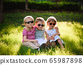 Smiling kids at the garden in sunglasses 65987898