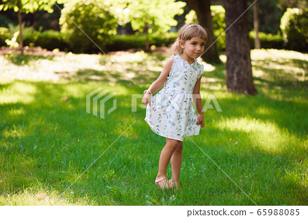 Sweet little girl outdoors with curly hair in the wind. 65988085