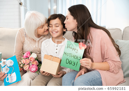 Blissful boy being kissed by his female parent and grandma 65992181