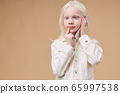 thoughtful dreamy child with albinism syndrome talking on phone 65997538