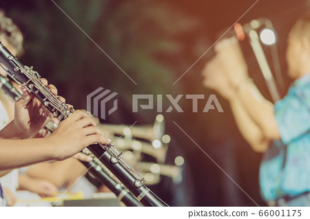 Male student with friends blow the clarinet with the band for performance on stage at night. 66001175