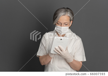 Gray-haired female doctor working with notepad. Caucasian woman wearing white protective uniform, mask and goggles using digital tablet. Isolated on gray back with copyspace on left 66007393