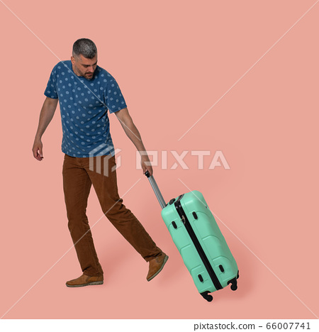 Attractive man carries plastic suitcase on wheels holding it by telescopic handle. Young Caucasian traveler in casual clothes with green suitcase looking at it. Advertising template with textspace 66007741