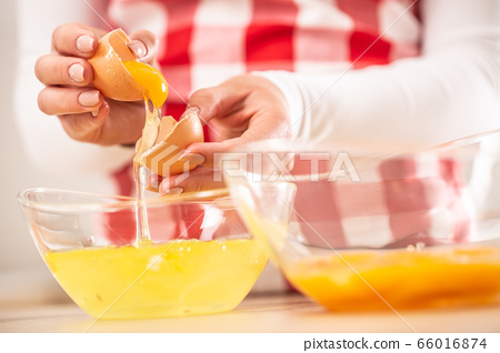 Detail of woman's hands separating egg yolks from 66016874