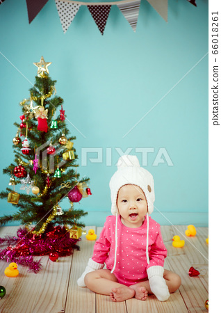 Little baby in knit winter clothing with knitted beanie and Decorating Christmas tree on green background 66018261