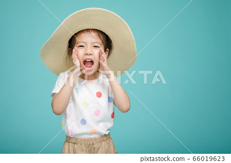 Excited Asian little girl is announcing telling a secret or shouting, empty space in studio shot isolated on colorful blue background 66019623