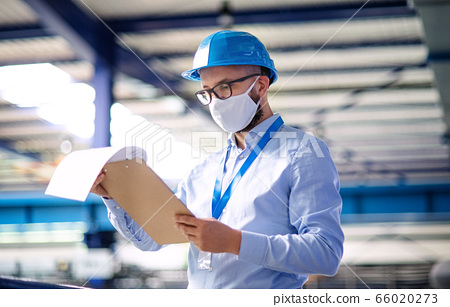 Technician or engineer with protective mask and helmet working in industrial factory. 66020273