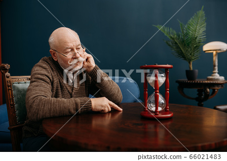 Elderly man looking on sandglass in home office 66021483