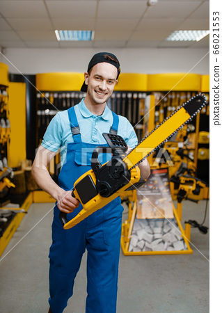 Male worker holds chainsaw in tool store 66021553
