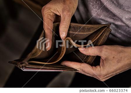 Empty wallet in the hands of an elderly man. 66023374