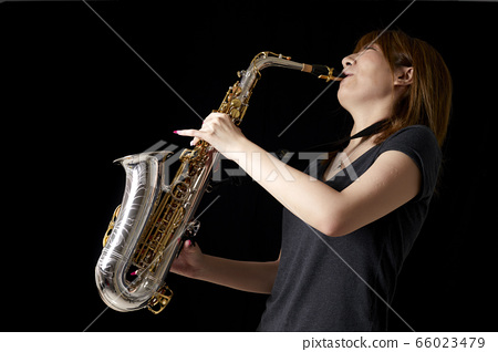 Young Japanese woman playing the saxophone 66023479