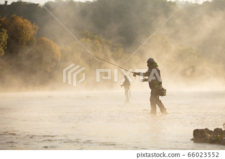 Men fishing in river with fly rod during summer 66023552