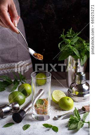 Sifting sugar in a homemade refreshing mojito 66025271