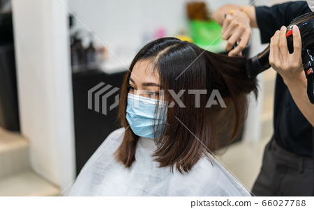 hairdresser using hair dryer and comb to the hair 66027788