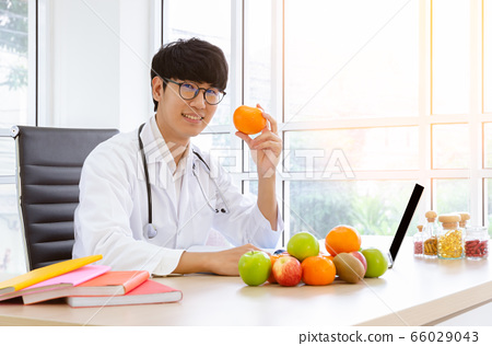 Male nutritionist sitting at clinic desk and  66029043