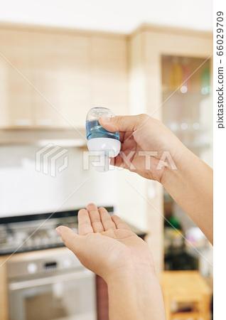 Woman applying anti-bacterial hand gel 66029709