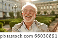 Don't stop laughing! Portrait of happy and handsome senior man in glasses looking at camera and smiling while standing outdoors on a sunny day 66030891