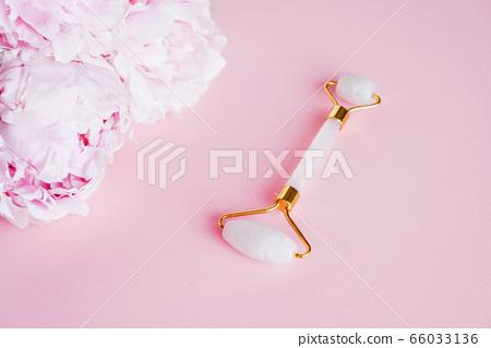 Jade stone roller made of pink quartz on pink background. 66033136