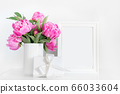 Pink peony in white vase, gift and photo frame. 66033604