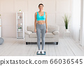 Slim Woman Weighing Herself Standing On Scales At Home 66036545