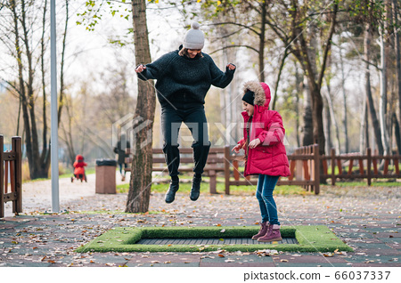 Mom and her daughter jumping together on trampoline in autumn park 66037337