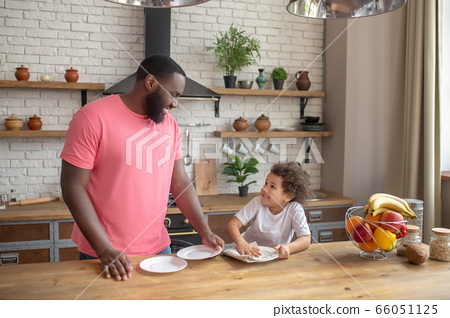 Tall dark-skinned man in a pink tshirt standing and smiling , while his kid wiping the plate 66051125