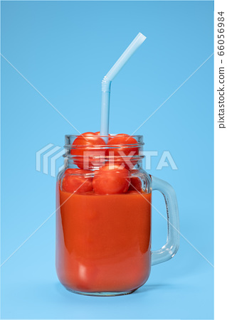 tomato juice with fresh tomatoes in a mug on a blue background 66056984