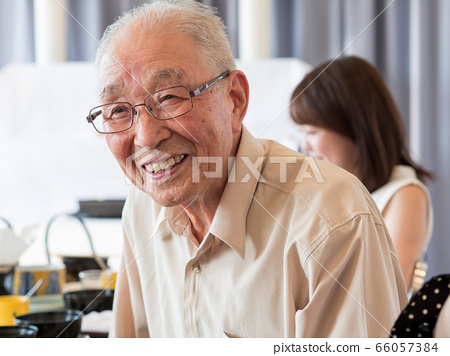 An old man talking animatedly at a family event 66057384