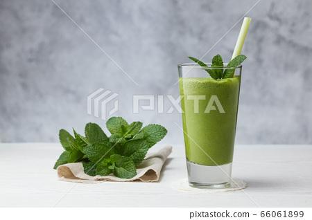 Freshly blended green fruit smoothie in glass. 66061899