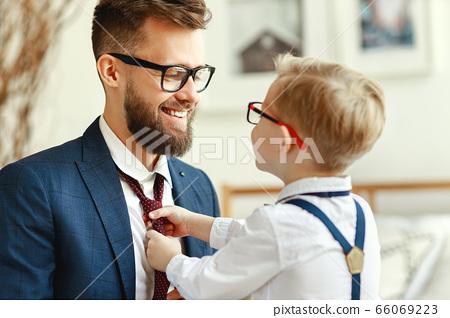 happy son helps father tie a necktie at home. 66069223