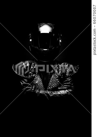 Portrait of a young female biker wearing a studded leather jacket and a black helmet 66070087