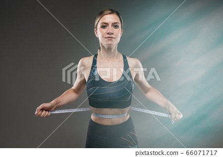 Sport caucasian girl with slim figure measures a waist isolated on black background 66071717