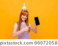 red-haired girl with a festive cap on her head holds a phone with a mockup on a yellow background 66072058