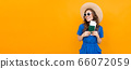 horizontal photo of a tourist girl in a blue dress with sunglasses and a straw hat on her head on a 66072059
