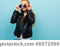 cheeky european girl in glasses on a light blue wall 66072060