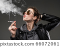 A young girl with rough facial features in a black jacket smokes isolated on black background 66072061