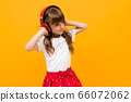 attractive girl enjoys listening to music on headphones on an orange studio background 66072062