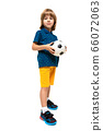 young european cute child in sportswear is standing and holding a soccer ball in his hands on a 66072063