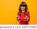 Beautiful little girl in dress plays with glasses isolated on yellow and orange background 66072066