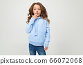 surprised european teenager girl in blue hoodie with open mouth on a white background with copy 66072068