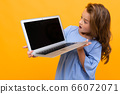 girl in surprise looks at a laptop screen with a mockup on a yellow background 66072071