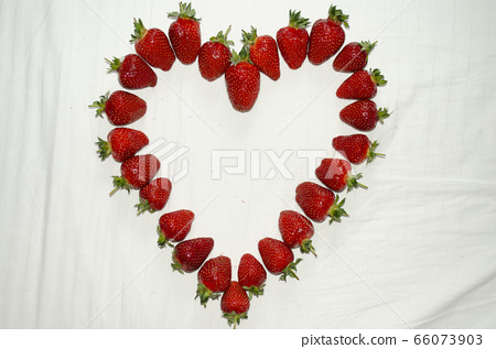 Ripe strawberries are laid out on a white background in the shape of a heart 66073903