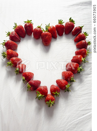 Ripe strawberries are laid out on a white background in the shape of a heart 66073905