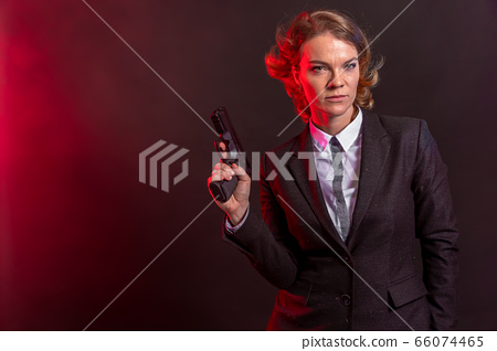 business woman with a gun in his hand. portrait on a black background. copy space 66074465