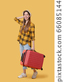 Young adult girl in a plaid shirt with a red suitcase. 66085144