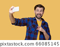 Cheerful grimacing man taking a selfie on a smartphone. 66085145